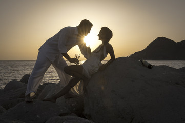 Silhouette of young couple having drinks on beach at sunset