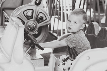 Monochrome image of little boy driving toy child car