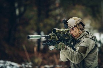 armed  man in camouflage with sniper gun