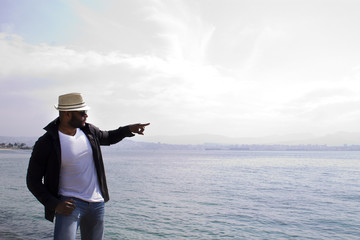 black man pointing to the sea