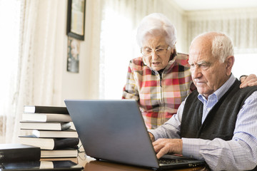 Senior couple working with Laptop and books at home
