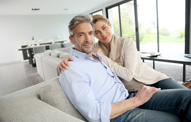 Portrait of 45-year-old couple relaxing in modern house