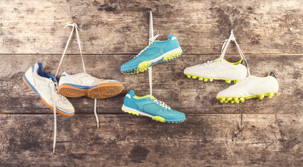 Sports shoes hang on a nail on a wooden fence background