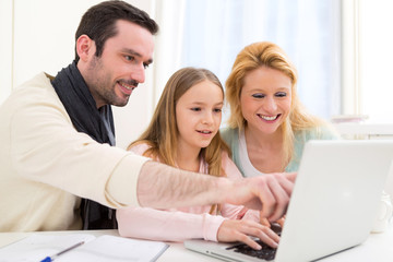 Happy family in front of a laptop