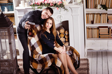 A young beautiful couple is making interior selfie by retro came
