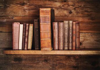 Bücher auf altem Holzregal.
