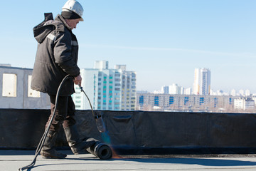 Roofer man worker installing roll of roofing felt