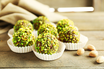 Fototapete - Tasty homemade pistachio candies on wooden table