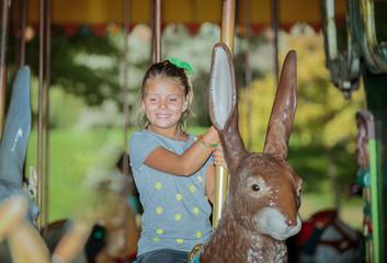 Funny joyful little girl riding on easter bunny carousel