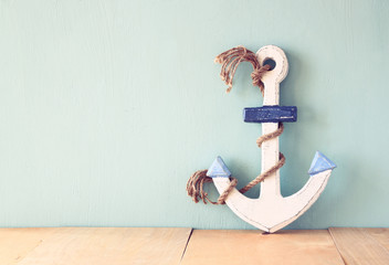old nautical anchor on wooden table over wooden aqua background