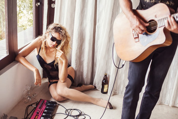 beautiful sexy girl and her boyfriend playing guitar