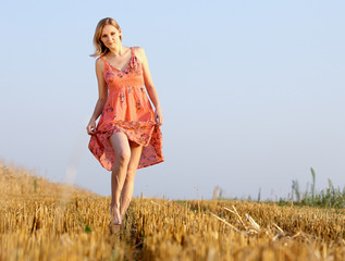 Beautiful young woman on summer dress standing