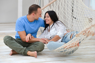 Woman relaxing in hammock smiling and man sitting