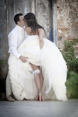 Happy newly wed couple kissing outdoors against old building