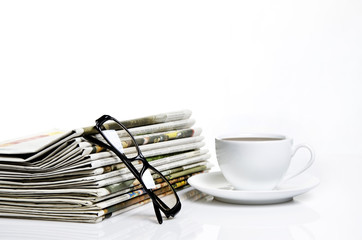 glasses and newspapers with a cup of coffee