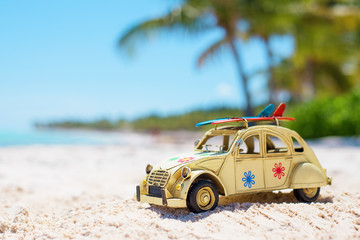 Small toy car on the beach with surfboards on the roof