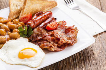 Full english breakfast with bacon, sausage, fried egg, baked bea
