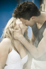 Happy young couple standing kissing outdoors against blue house