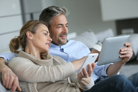 Mature couple at home using smartphone and tablet