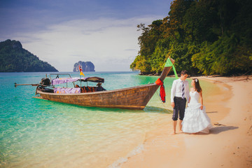 bride and groom stand near longtail boat