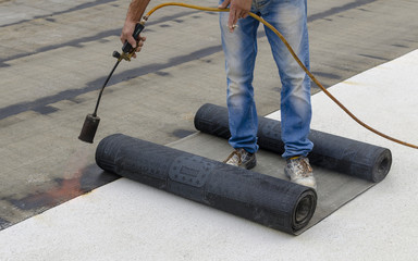 Worker preparing part of bitumen roofing felt roll