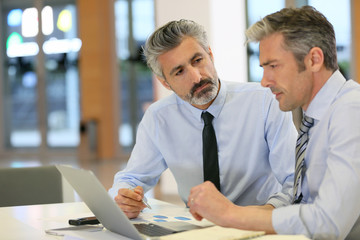 Businessmen working in office with laptop