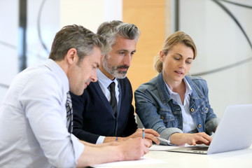 Business people in a work meeting with laptop