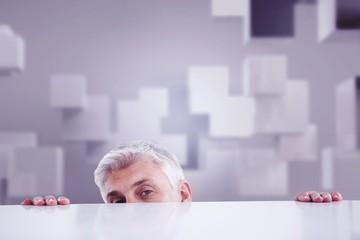 Composite image of businessman peeking over desk