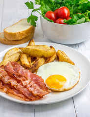 Hearty breakfast with bacon, fried egg, potato and vegetables