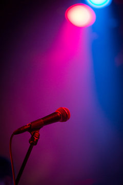 A band stage microphone highlighted by a pink and blue light