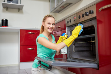 happy woman cleaning cooker at home kitchen