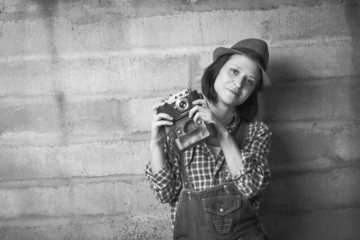 Indoor portrait of woman with vintage camera in a black and whit