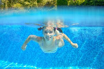 Girl swims in pool underwater, kid swimming, children sport