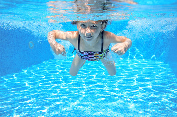 Girl swims in pool underwater, kid swimming, children sport