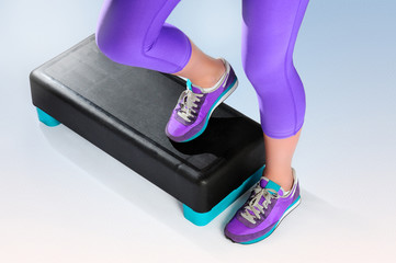 Female feet do exercise on fitness aerobic stepper.