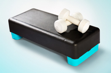 White dumbbells lie on a black-turquoise aerobic step.