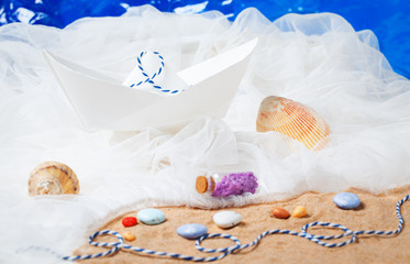 paper boat with sand, ropes, water