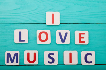 Phrase I love music on blue wooden background. Top view