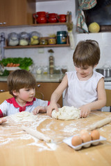Cute Boy Learning From His Brother How to Knead Dough