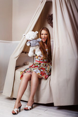 A glamour young girl is sitting on a bed, holding a teddy bear a
