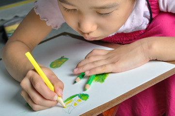 closeup little asian girl hand draw her  picture with color penc