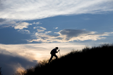 Silhouette of person heavy walking toward the summit