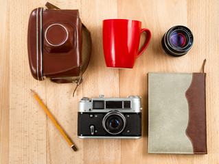 retro journalist workspace with camera, lens, notebook, pencil a