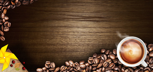 Coffee cup and coffee beans on a wooden table. Dark background