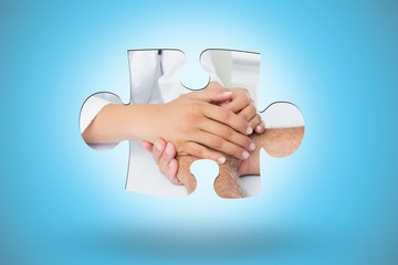 lose-up mid section of a doctor holding patients hands