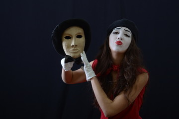 the girl is MIME holding a theatrical mask with hat