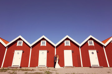 Bride and groom near red houses in a rpw