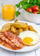 Hearty breakfast with bacon, fried egg, potato and orange juice