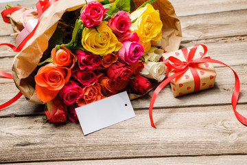 Bunch of roses and gift box with an empty tag