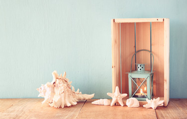 Old nautical lantern and shells on wooden table over wooden aqua